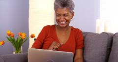 Black grandmother laughing and talking on laptop - stock photo