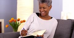 Mature black woman writing in journal - stock photo