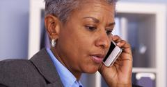 Senior Black businesswoman talking on smartphone - stock photo