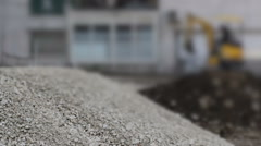 Construction site with a small backhoe moving in a de-focused background Stock Footage