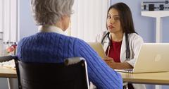 Mexican woman doctor talking with senior patient Stock Photos