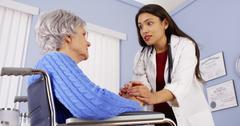 Hispanic woman doctor comforting disabled elderly patient Stock Photos