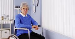 Disabled senior woman sitting in wheelchair Stock Photos