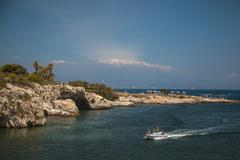 Sea craft move in a gulf with rock-ribbed coast - stock photo