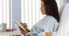 African American woman using tablet computer in hospital bed - stock photo