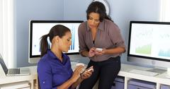 Mexican and African American business women using mobile phones and working - stock photo