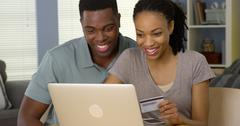 Smiling young black couple using credit card to make online purchases Kuvituskuvat