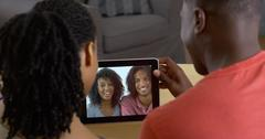 African American couple talking to friends over tablet computer video chat Kuvituskuvat