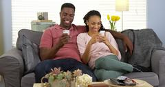 Happy young black couple relaxing on couch using smartphones Kuvituskuvat