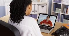 Female patient talking to African American doctor over video chat Kuvituskuvat