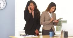 Two mixed race colleagues talking on smartphone and using tablet Stock Photos
