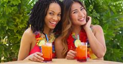 Black and Asian best friends enjoying tropical vacation together Stock Photos