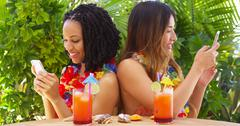 Black and Asian best friends on vacation using mobile phones Stock Photos
