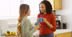 African American and Asian friends sipping coffee in kitchen Stock Photos