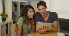 Stock Photo of Happy mixed race couple talking on tablet
