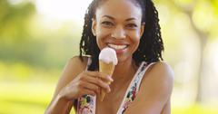 Black woman smiling and eating ice cream - stock photo