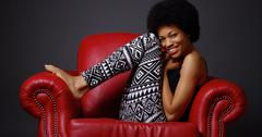 African woman sitting in red armchair Stock Photos