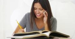 Hispanic woman calling friend for help with homework Stock Photos