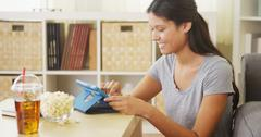 Hispanic woman laughing and using tablet on coffee table Stock Photos