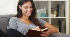 Mixed race woman sitting on couch writing in journal Stock Photos