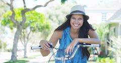 Young woman smiling on bike Stock Photos