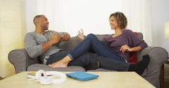 Black couple using electronic devices on couch Stock Photos