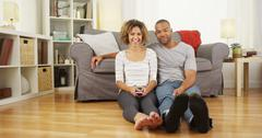 Cute African couple sitting on floor in living room Stock Photos