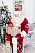 saint nicolas with gifts sits near the christmas fir-tree - stock photo