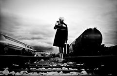 Croatia, Woman walking along rails with guitar on her shoulder Stock Photos