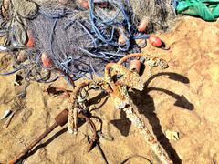 Oman, Muscat, Fishing net and anchors on beach Stock Photos