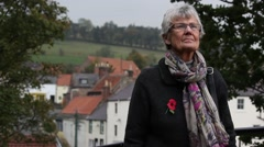 Stock Video Footage of Elderly lady wearing poppy looking up at memorial