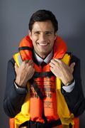Businessman wearing life jacket Stock Photos