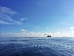 Oil platform with supply vessel nearby during daytime - stock photo