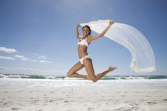 Woman Jumping At Beach - stock photo