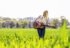 Female country singer in grass field Stock Photos