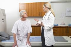 Female doctor talking to male patient next to MRI Scanner Stock Photos
