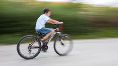boy cyclist in traffic on the city roadway - stock photo