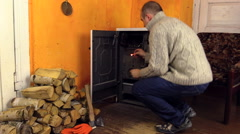 Villager man in sweater light firewood in stove with match Stock Footage