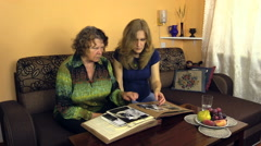 Young pregnant woman looking at photo album with senior grandma Stock Footage