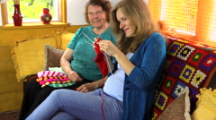 Happy old woman spend time knitting with pregnant granddaughter - stock footage