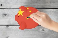 China saving concept with little hand dropping a coing into piggy bank overla Stock Photos