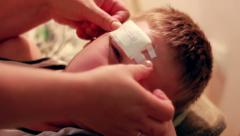 Mother Putting Bandage On Child Stock Footage