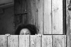 Spain, Barcelona, Little girl (4-5) hiding behind door, playing hide and seek Stock Photos