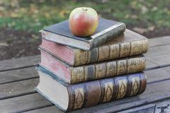 Apple sitting atop pile of old books - stock photo