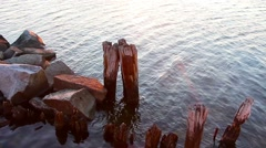 Stones and old wooden pillars on the sea Stock Footage