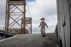 USA, Louisiana, New Orleans, Boy (2-3) running down from levee in Lower ninth Kuvituskuvat