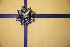 Gold gift wrapped with blue bow Stock Photos