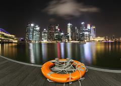 Singapore, Marina Bay, Skyline at night with lifebelt in front - stock photo