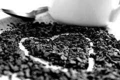 A heart drawn in coffee granules alongside a small silver spoon and white mug Stock Photos