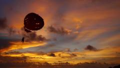 Beautiful sunset on the beach and people taking a parachute in the sky - stock footage